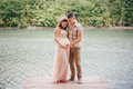 Young pregnant woman with her husband standing near lake women in a pink dress on a berth kissing Royalty Free Stock Image