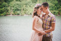 Young pregnant woman with her husband standing near lake women in a pink dress on a berth kissing Stock Photography