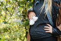 Young pregnant woman holding baby booties on her abdomen. Royalty Free Stock Photo