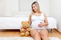 Young pregnant woman sitting on the floor with a teddy bear Royalty Free Stock Photo