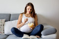 Young pregnant woman, sitting at home on the couch, eating melon Royalty Free Stock Photo