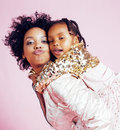 Young pretty african-american mother with little cute daughter hugging, happy smiling on pink background, lifestyle Royalty Free Stock Photo