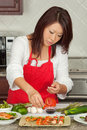 Young Pretty Asian Woman Preparing in Kitchen Stock Images