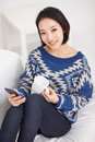 Young pretty Asian woman with smart phone. Royalty Free Stock Photo