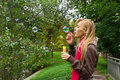 Young pretty blond woman blowing soap bubbles in park Royalty Free Stock Photo