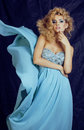 Young pretty blond woman in blue luxury dress