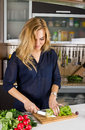 Young pretty blond woman cooking salad in kitchen Stock Photo