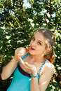 Young pretty blond woman eating strawberry at summer garden under tree Royalty Free Stock Images