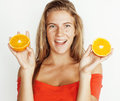 Young pretty blond woman with half oranges close up isolated on white bright teenage smiling Royalty Free Stock Photo