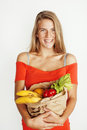 Young pretty blond woman at shopping with food in paper bag isolated on white smiling bright, lifestyle people concept Royalty Free Stock Photo