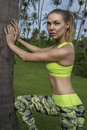 Young pretty blonde happy female wearing exercise clothing stretching leaning against palm tree during beautiful summer day. Royalty Free Stock Photo