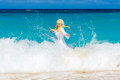 Young pretty blonde with long hair in white dress enjoy swimming the waves on a tropical beach Stock Images