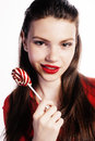 Young pretty brunette girl with red candy posing on white background isolated Royalty Free Stock Photo