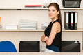 Young pretty business woman businesswoman sitting at desk and working smiling and looking at camera Stock Photo