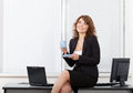 Young pretty business woman in the office with Royalty Free Stock Photo