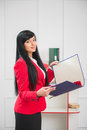 Young pretty business woman in red vertical portrait of with smile jacket standing the office with a blue folder with copy Stock Image