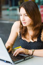 Young pretty caucasian lady using laptop outdoors Stock Photos
