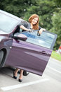 Young pretty curly haired woman standing behind a car with opened door Royalty Free Stock Photography
