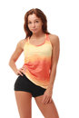 Young pretty fitness model in orange top and black shorts Royalty Free Stock Photography