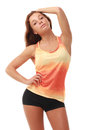 Young pretty fitness model in orange top and black shorts Royalty Free Stock Photos