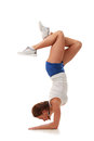 Young pretty fitness model in white top and blue shorts performing a handstand whole body profile Royalty Free Stock Photo