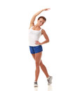 Young pretty fitness model in white top and blue shorts stretching a side Royalty Free Stock Photography