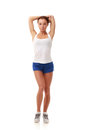 Young pretty fitness model in white top and blue shorts stretching a triceps Stock Photos