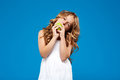 Young pretty girl eating green apple over blue background. Royalty Free Stock Photo