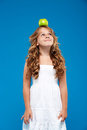 Young pretty girl holding apple  on head over blue background. Royalty Free Stock Photo