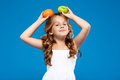 Young pretty girl holding apple and orange over blue background. Royalty Free Stock Photo