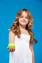 Young pretty girl holding green apple over blue background. Royalty Free Stock Photo