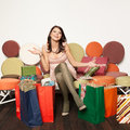 Young pretty girl sitting on a sofa with shoppings bags Royalty Free Stock Photography