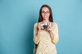 Young pretty girl taking photo using photocamera over blue background Royalty Free Stock Photo
