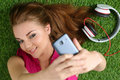 Young pretty girl taking self portrait with her smart phone laying on grass focus on face Stock Images