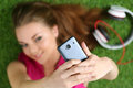 Young pretty girl taking self portrait with her smart phone laying on grass focus on phone Stock Image