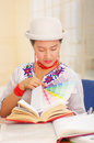 Young pretty girl wearing white shirt with colorful flower decorations and fashionable hat smiling, sitting by desk Royalty Free Stock Photo