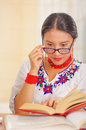 Young pretty girl wearing white shirt with colorful flower decorations and glasses, sitting by desk reading book smiling Royalty Free Stock Photo