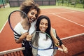 Young pretty girlfriends hanging on tennis court, fashion stylish dressed swag, best friends happy smiling together Royalty Free Stock Photo