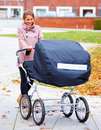 Young pretty lady walking baby around in pram Royalty Free Stock Photo