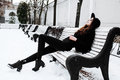 Young pretty modern hipster girl waiting on bench at winter snow park alone, lifestyle people concept Royalty Free Stock Photo