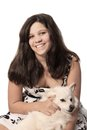 Young pretty pre teen girl brunette smiling holding her white furry dog on a white background Royalty Free Stock Image