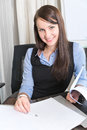 Young pretty smiling business woman with notebook in the office Royalty Free Stock Photo