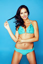 Young pretty smiling happy slim girl in bikini on blue background, lifestyle people on vacation concept Royalty Free Stock Photo