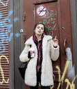 Young pretty stylish teenage girl outside in city wall with graffity smoking cigarette at forbidden smoke sighn Royalty Free Stock Photo