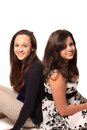 Young pretty teen girls that could be sisters of friends smiling both with long brown hair on a white background Stock Image