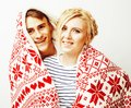Young pretty teenage couple at Christmas time warming in red decorated blanket, hipster guy with his girlfriend happy Royalty Free Stock Photo