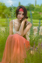 Young pretty teenage girl sitting against flowers Royalty Free Stock Photo