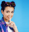 Young pretty teenage modern hipster girl posing emotional happy smiling on blue background, lifestyle people concept