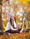 Young pretty woman on the autumn leaf sitting and reading book Stock Images