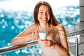 Young and pretty woman on the balcony smiling drinking milk blue water background Royalty Free Stock Images
